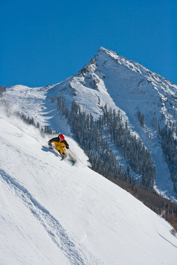 Skier on Crested Butte's steeps with the peak in the background