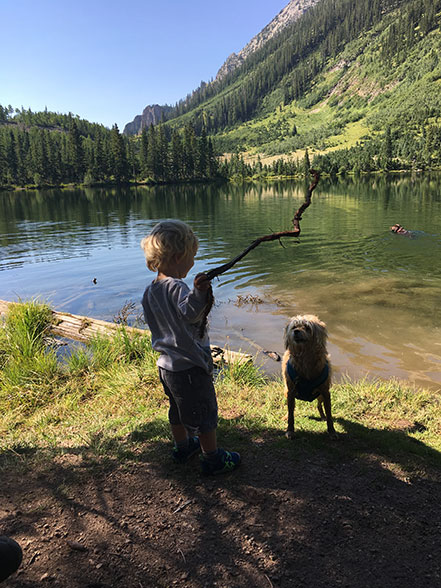 a young boy and his dog with a stick by Dollar Lake west of Crested Butte, Colorado