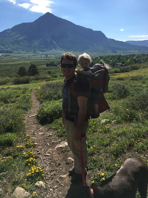 dad and kid hiking with Crested Butte in the background