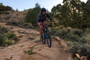 Crested Butte mountain biking female biker smiles as she rides downhill on a sandstone trail. The area is a high desert in summer.