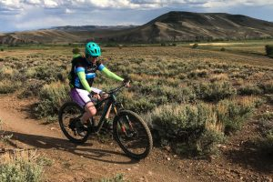 Beginner MTB trails in Crested Butte a female mountain biker rides on a smooth trail through sagebrush. Tenderfoot Mountain is in the background. It is summer.