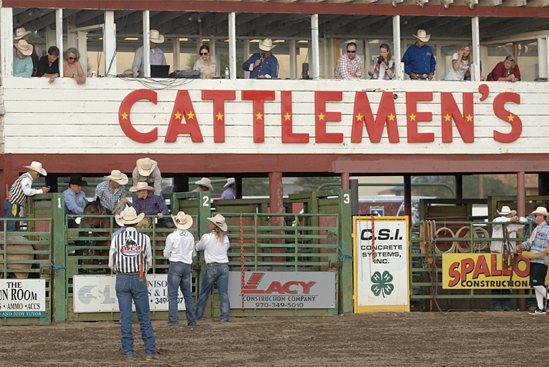 "Wide shot of ""Cattlemen's"" sign, announcer's booth and corrals at the rodeo."
