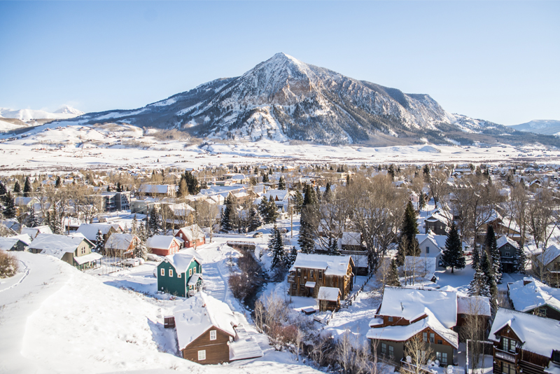 Photo of a snow-covered town with a mountain in the background.