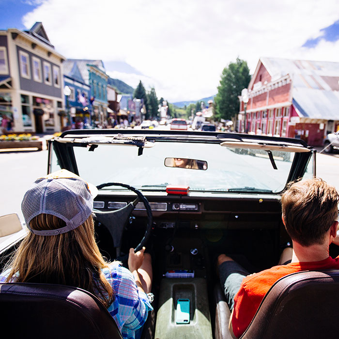 Two people in an open-air Scout International driving down Elk Avenue in Crested Butte