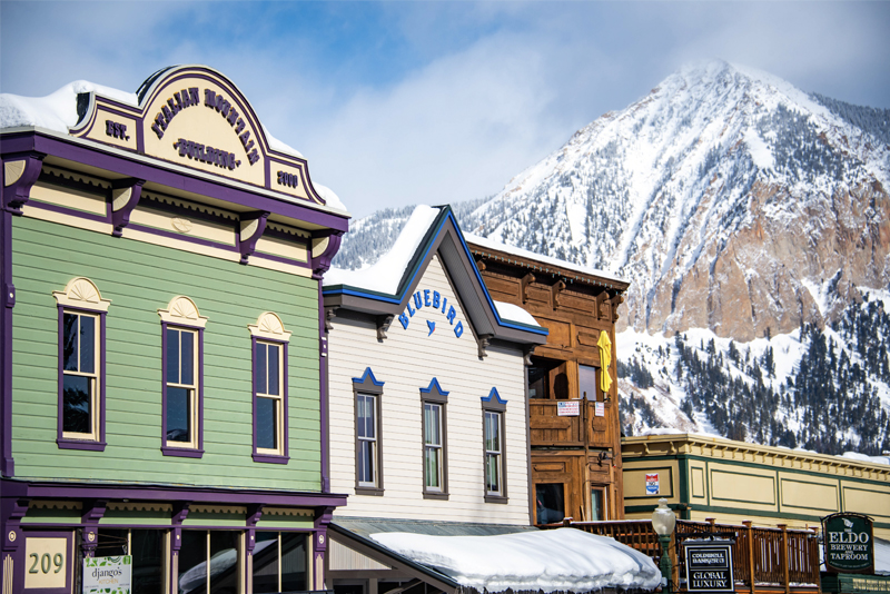 Photo of brightly painted building on the main street in Crested Butte in winter. Crested Butte (the mountain) is in the background.