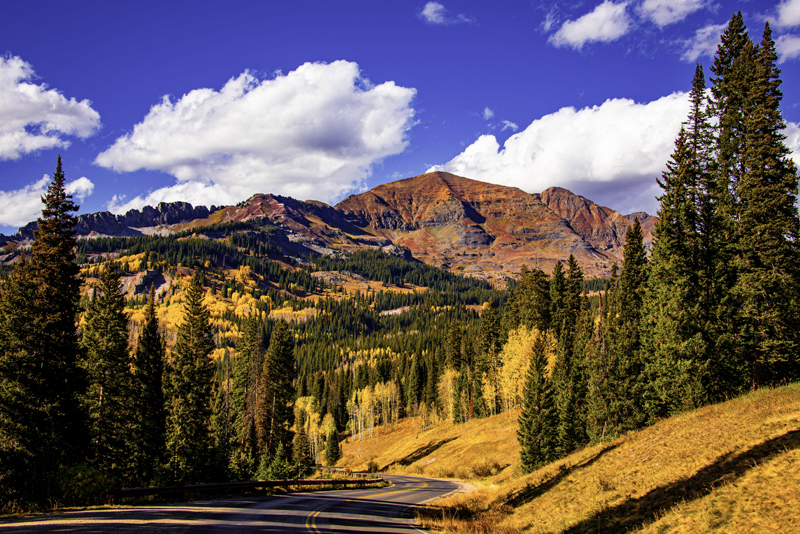 Crested Butte fall hiking photo of a huge red mountain with green spruce trees and yellow aspens in the foreground. A paved road winds through the trees.