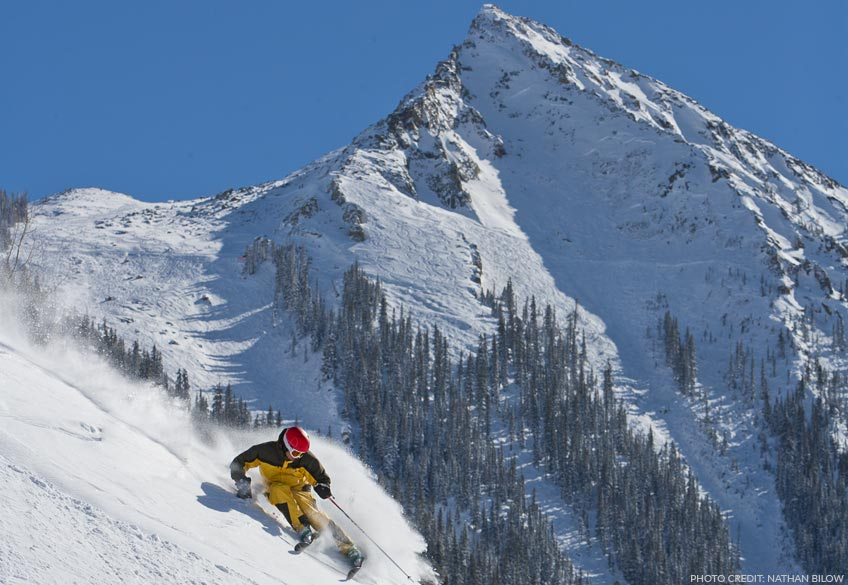 skier with peak of Crested Butte in the background