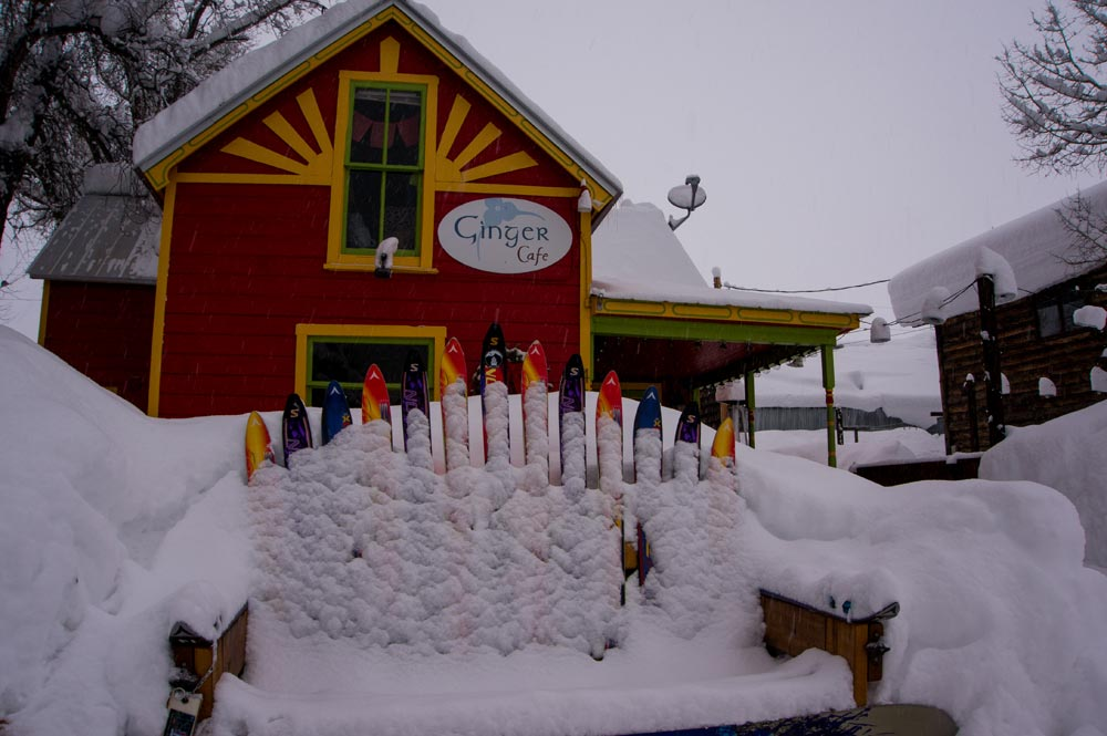 Ski chair covered in snow in front of the Ginger Cafe, CB