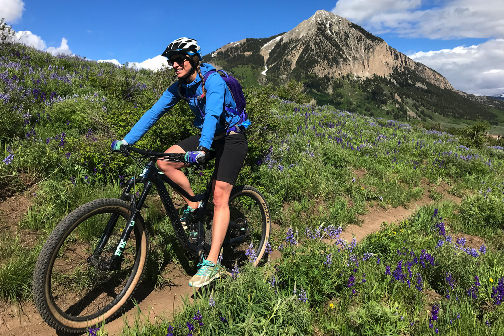 A woman smiles as she coasts down Lupine Trail on a bike in summer. Crested Butte is in the background.