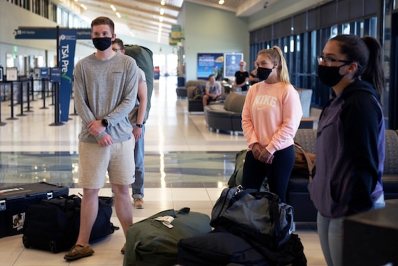 Photo of three people wearing masks and social distancing inside the airport.