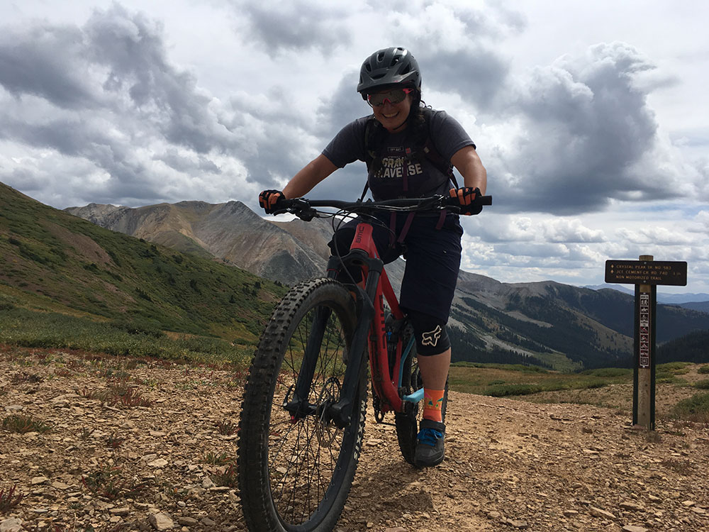 photograph showing Mel reaching the top of a climb on her mountain bike