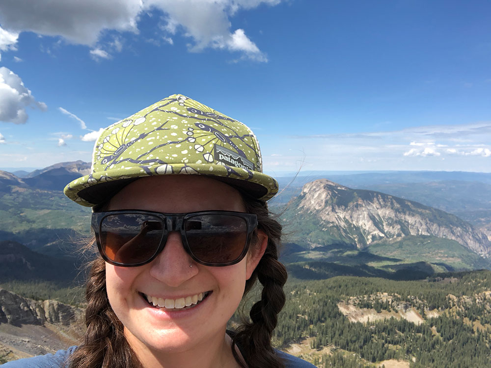 selfie of Mel at the top of a peak near Crested Butte, CO with other mountains in the background