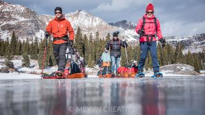 Journalists pulling sleds across icy Lake Irwin