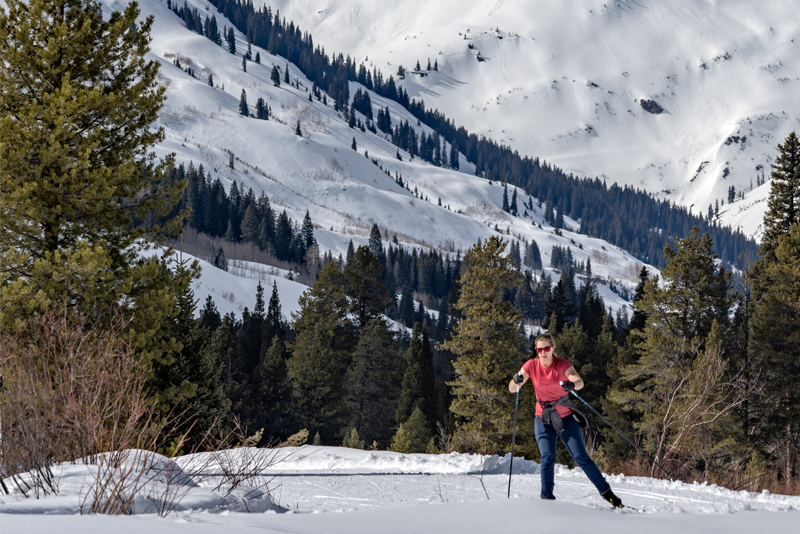 Photo of a woman nordic skiing on a groomed trail with snowy mountains in the background.