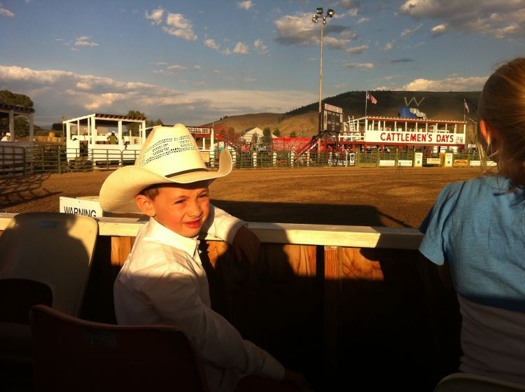 Kid sitting in VIP box at the rodeo