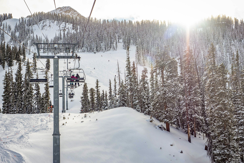 Photo of two people on a chairlift at sunrise with a peak in the background.