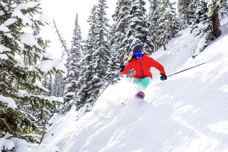 Photo of a woman in a red jacket skiing powder on steep terrain with trees.