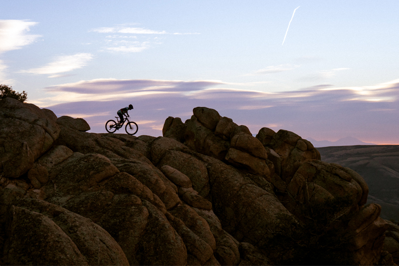 A mountain biker is silhouetted on the top of a rock formation at sunrise.