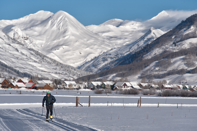 Photo of a nordic skier with Crested Butte's mountains in the background.