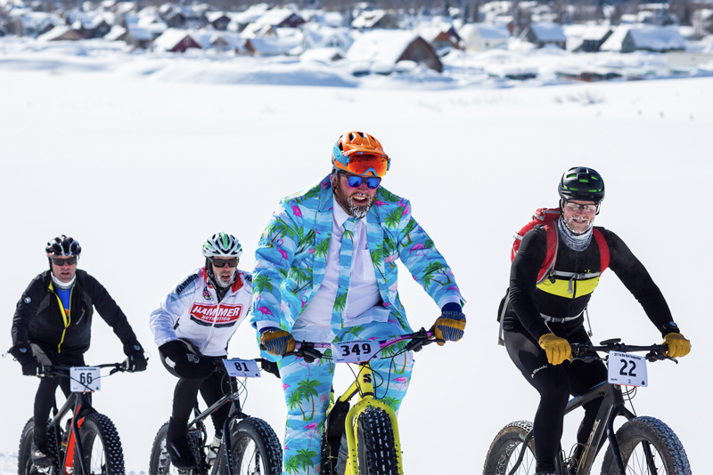Fat bikers with ice on their facial hair ride through the snow.