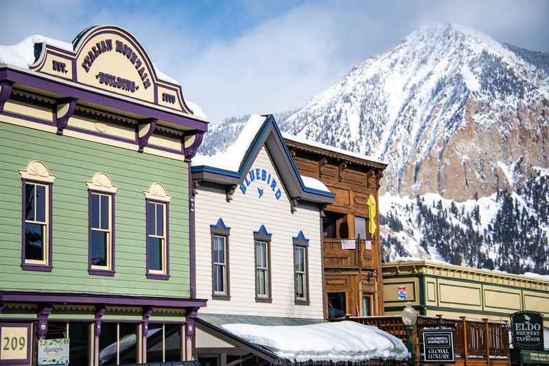 Crested Butte businesses with snowy Crested Butte (the mountain) in the background.